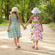 Two girls go hand in hand — Stock Photo