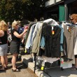 Stock Photo: Women shop for clothes at garage sale