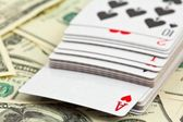Playing cards on a money background — Stock Photo