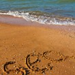 Sea word on a sandy beach - Stock Photo