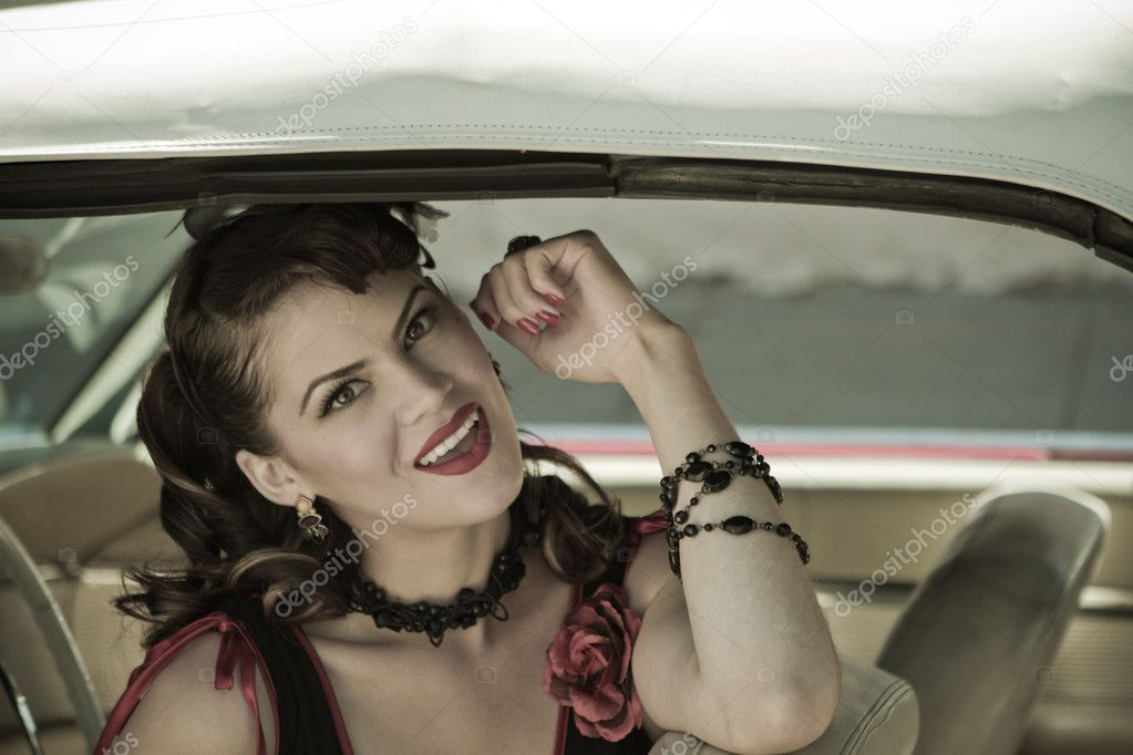 Beautiful Brunette woman looking out of a vintage car — Stock Photo #11317660