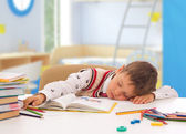 Schoolboy sleeping on the table with notebook — Stock Photo