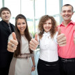 Stock Photo: Happy business team with thumbs up in the office