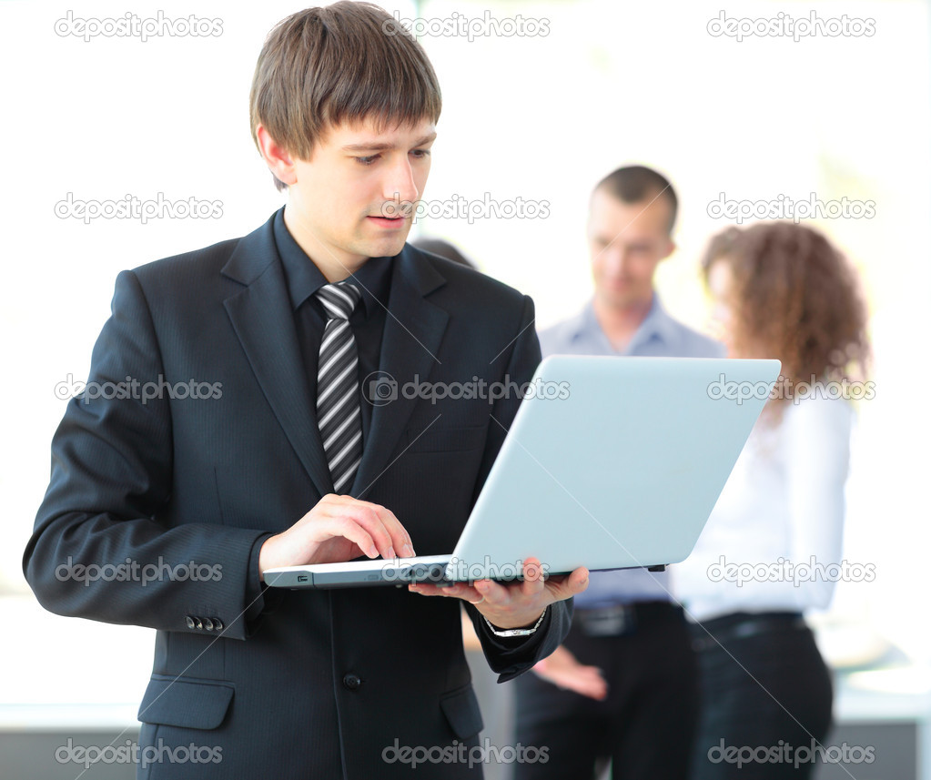 Portrait of a smart business man using laptop with colleagues in the background  Stock Photo #12172472