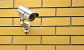 Camera on a brick wall of the house — Stock Photo