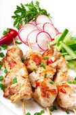 Chicken shish kebab with a garnish from vegetables — Stock Photo