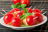 Tomato and cheese slices decorated with basil leaves on a plate — Stock fotografie