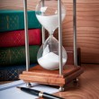 Hourglasses and book on wooden table — Stock Photo #11884847