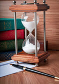 Hourglasses and book on a wooden table — Stock Photo