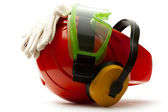 Red safety helmet with earphones, goggles and gloves — Stock Photo