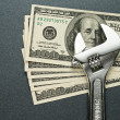Spanner and dollars - Stock Photo