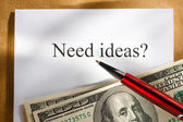 Idea conception with pen and money — Stock Photo