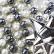 String of black and white pearls with bow — Stock Photo