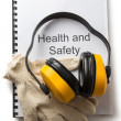 Stock Photo: Health and safety register with earphones