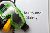 Health and safety register with goggles and earphones — Stok fotoğraf