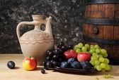 Ceramic jug, barrel and fruit — Stock Photo