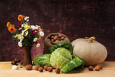 Flowers in a important on the table and pumpkin — Stock Photo
