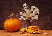 Pumpkins, corn and flowers on the table — Stock Photo