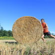 Royalty-Free Stock Photo: Man pushing hay bale