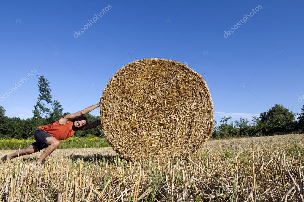 Effort concept, sporty man pushing a hay bale uphill — Stock Photo #11849546