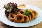 Golden onion rings with sauce — Stock Photo