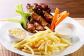 Chicken wings with fries and vegetable — Stock Photo