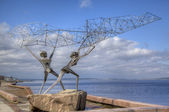 Sculpture of TWO FISHERMEN, CASTING A NET INTO THE LAKE in Petrozavodsk. Karelia, Russia — Stock Photo