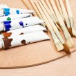 Tubes of colorful paint and paint brush - Stock Photo