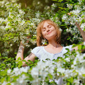 Young blonde woman with the apple tree on a warm summer day — Stock Photo