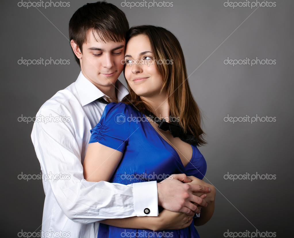Happy young couple standing together against a grey wall  Stock Photo #10992297