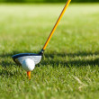 Close up on golf ball on a tee and golf club behind - Stock Photo