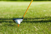 Close up on golf ball on a tee and golf club behind — Stock Photo