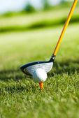 Close-up na bola de golfe em um t-shirt e clube de golfe atrás — Foto Stock