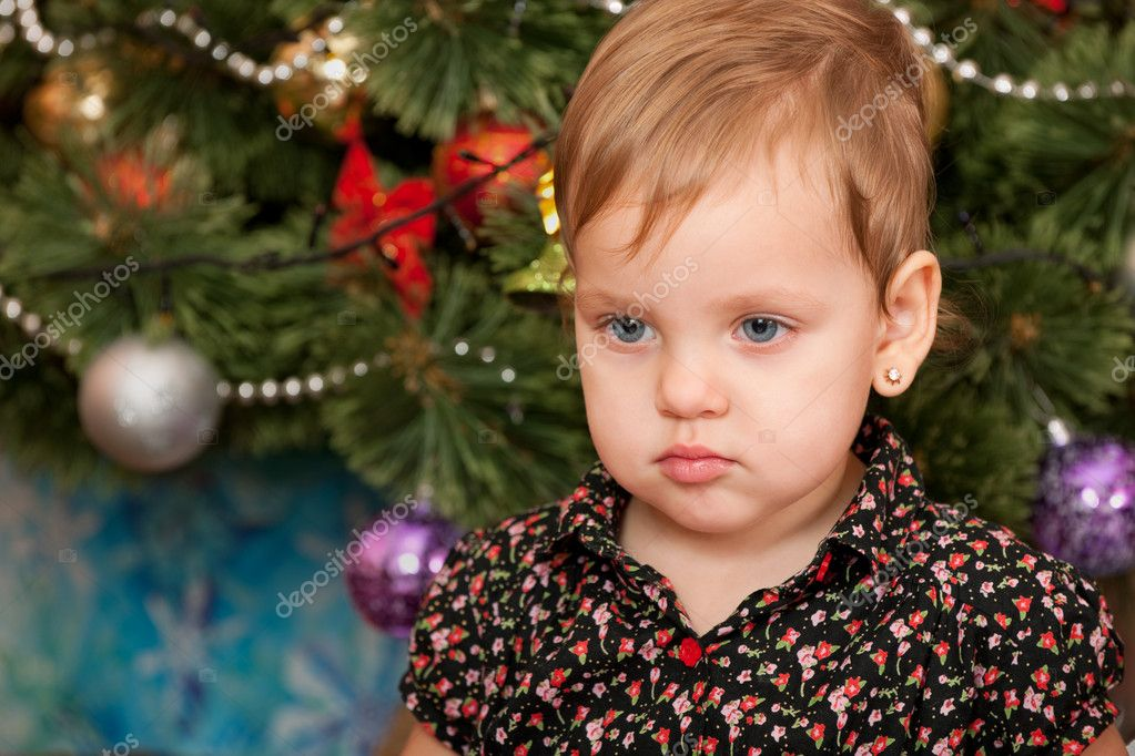 A portrait of a serious little girl at the christmas tree — Стоковая фотография #11543184