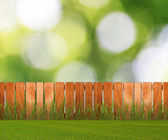 Green grass in garden with fence near the brick wall — Stock Photo