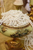 Luxury vase full thread pearls on table — Stock Photo