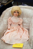 Vintage doll in vintage chair at flea market. — Stock Photo