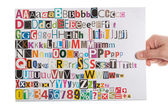 Hand holding newspaper clippings alphabet — Stock Photo
