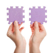 Hands holding foam puzzle pieces — Stock Photo