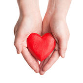 Red wooden heart in woman's hands — Stock Photo