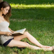 Stock Photo: Young brunette enjoying book outdoors.