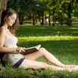 Young brunette enjoying book outdoors. — Stock Photo #12158013