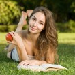 Cute young brunette in the park reading. — Stock Photo #12305643