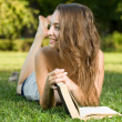 Cute young brunette in the park reading. — Stock Photo #12305648