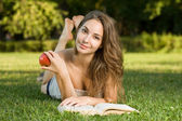 Cute young brunette in the park reading. — Stock Photo