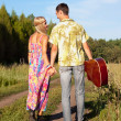 Young woman and man with guitar go on road — Stock Photo