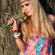 Beautiful blonde with flowers stand by tree - Stock Photo