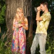 Fine blonde with flowers stands by treeand young man holding fi — Stock Photo