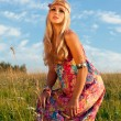 Beautiful blonde woman posing in meadow against blue sky — Stock Photo