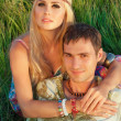 Cute young man and fine woman sit on meadow. — Foto Stock
